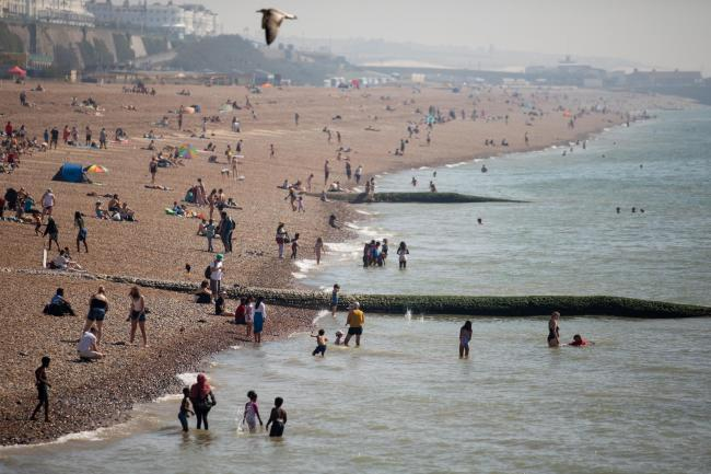 People enjoying the sun on Brighton beach as the UK basks in the late summer heat (Steve Paston/PA)